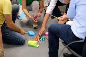 Personnes prennent post-it et crayons pour atelier collaboratif